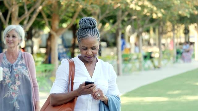 Independent senior woman walks in city park