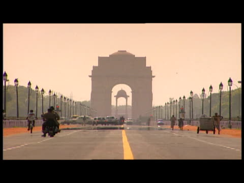 India Gate in heat haze with traffic in foreground New Delhi