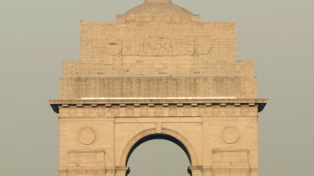 ms td india gate, war memorial commemorating soldiers of british indian army who died in world war i, traffic in in foreground / delhi, india - 戦争記念碑点の映像素材/bロール