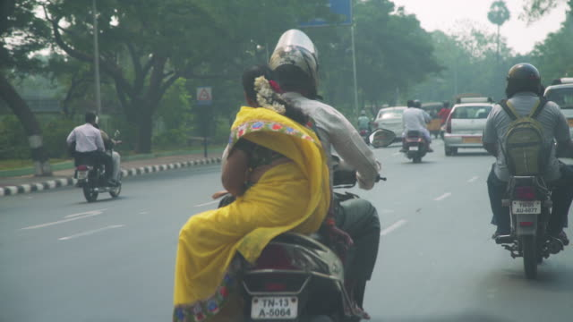 India iconic image of woman and man in a motorcycle with traditional sari clothing. Chennai india, road from a car