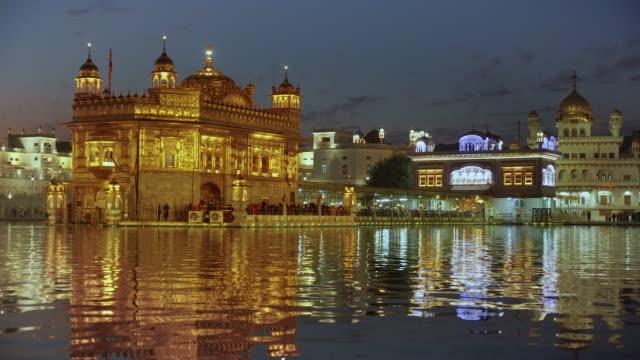 india, punjab, amritsar, (golden temple), the harmandir sahib, amrit sagar (lake of nectar), illuminated at dusk - punjab region stock-videos und b-roll-filmmaterial