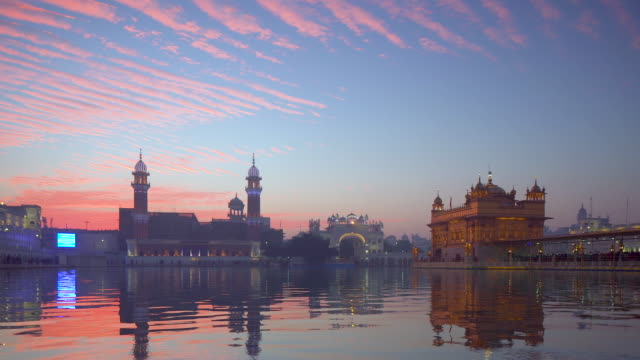 india, punjab, amritsar, (golden temple), the harmandir sahib, amrit sagar (lake of nectar), illuminated at dusk - punjab india stock videos and b-roll footage