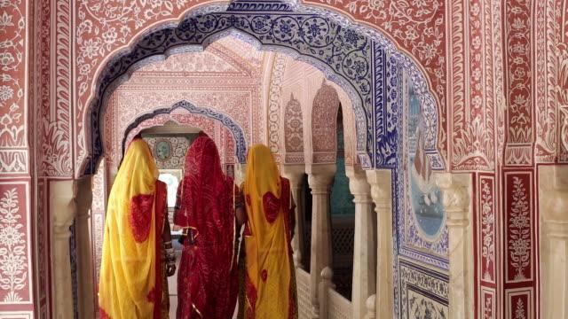 India, Rajasthan, Jaipur, Samode, ladies wearing colourful saris in ornate passageway
