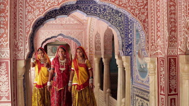 India, Rajasthan, Jaipur, Samode, ladies wearing colourful saris in ornate passageway