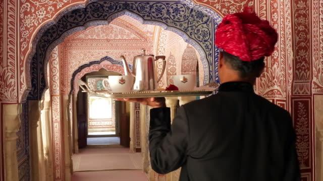 India, Rajasthan, Jaipur, Samode, waiter carrying tea tray in ornate passageway