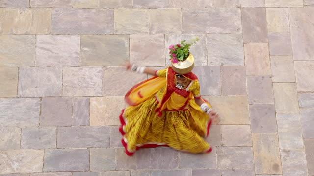 India, Rajasthan, Jaipur, Samode, woman wearing colourful sari dancing