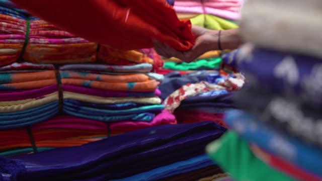 vídeos de stock, filmes e b-roll de india silk clothing shop market. men working bending the clothing and selling - vendedor trabalho comercial