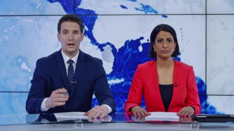 ld indiska anchorwoman och kaukasiska anchorman presenterar nyheter - journalist bildbanksvideor och videomaterial från bakom kulisserna