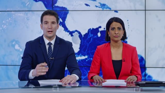 ld indian anchorwoman and caucasian anchorman presenting the news - mass media video stock e b–roll
