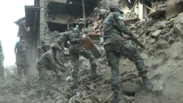 indian army digs away at rubble from a destroyed home to clear way for the road / a major earthquake hit kathmandu mid-day on saturday, april 25th,... - major road bildbanksvideor och videomaterial från bakom kulisserna