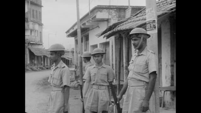 Indian Army stand outside a dilapidated street scene milling about expectantly