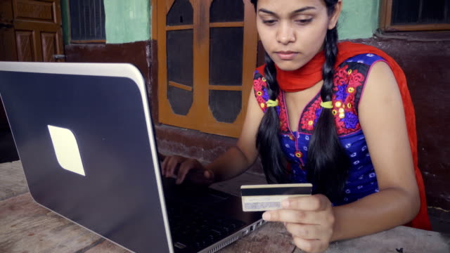 Indian Asian young woman doing online shopping at home.