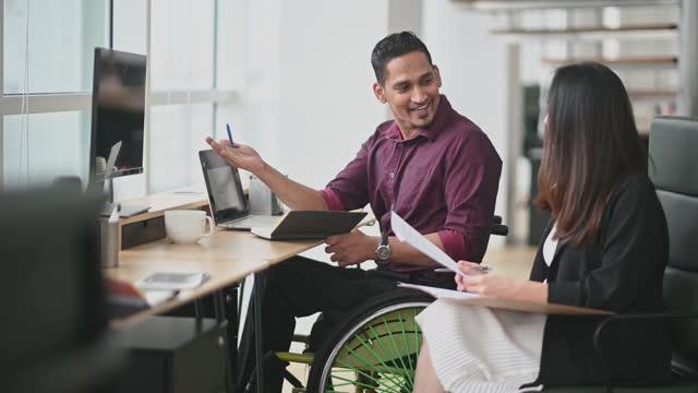 indian businessman in wheelchair having discussion with his female chinese colleague in creative office - blandat ursprung bildbanksvideor och videomaterial från bakom kulisserna