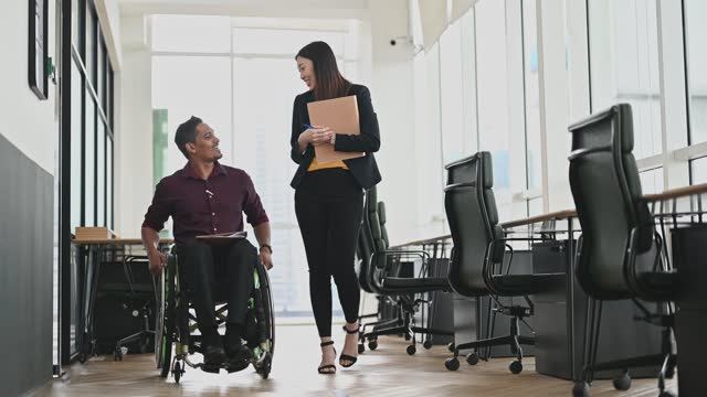 indian businessman in wheelchair walking with female colleague  discussing  at workplace - diversity stock videos & royalty-free footage