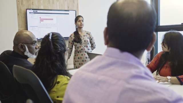 indian businesswoman explaining to colleagues in meeting - indian subcontinent ethnicity stock videos & royalty-free footage