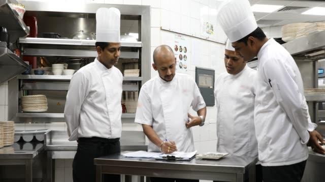 indiska kockar matlagning i ett professionellt kök i en gourmetrestaurang - skicklighet bildbanksvideor och videomaterial från bakom kulisserna
