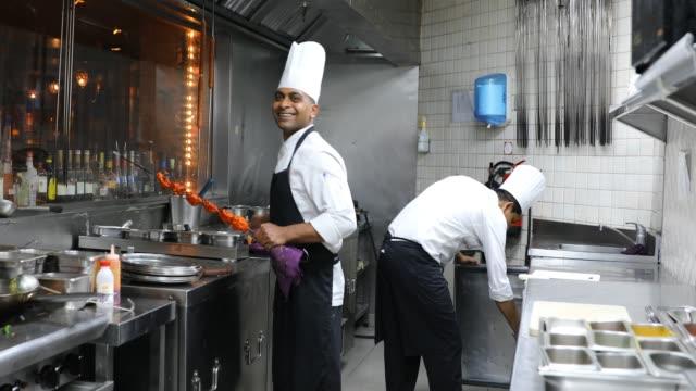 stockvideo's en b-roll-footage met indiase chef-koks koken in een professionele keuken van een gastronomisch restaurant - chinese culture