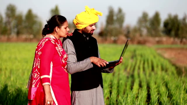 Indian couple standing in green field holding laptop