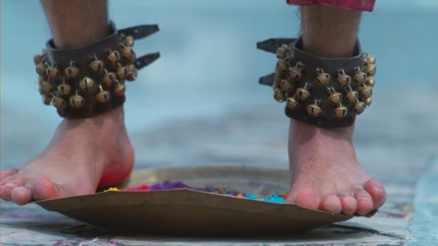 ECU of Indian Dancer's feet dancing on metal tray with holi colors