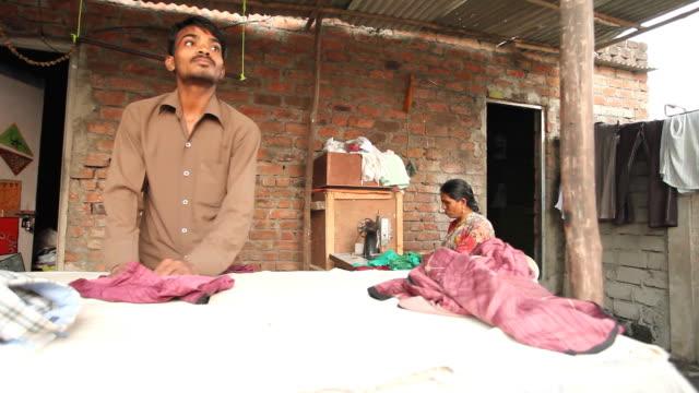Indian Dhobi Waschmaschine Mann und eine Frau mit Nähmaschine