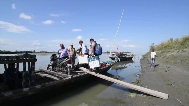 Indian election officials carry Electronic Voting Machines on a boat as security personnel watch over to reach remote polling stations in Lohore...