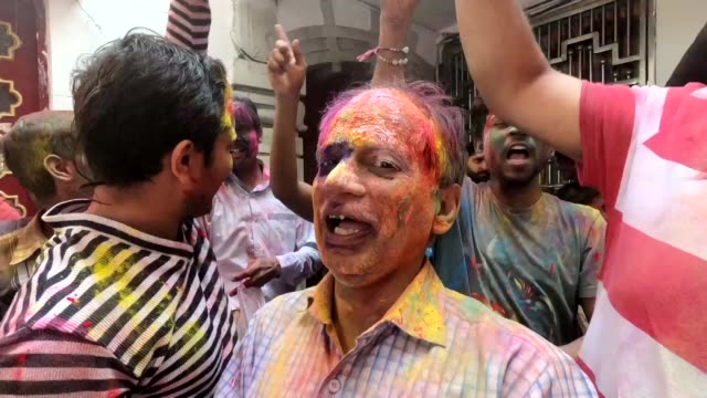 Indian families cover each other in coloured powder as they celebrate Holi the Hindu spring festival of colours during a traditional gathering at a...