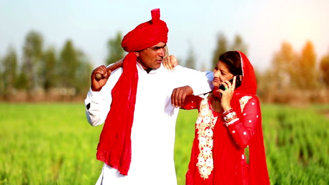 Indian farmer standing in the field with his wife