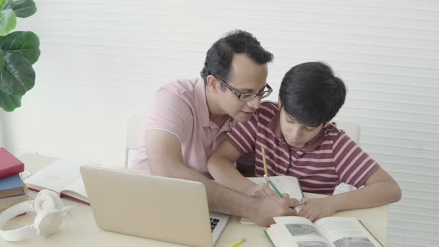 indian father teaches son homework. - son stock videos & royalty-free footage