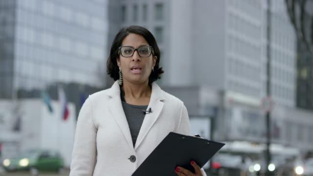 vídeos de stock, filmes e b-roll de notícias feminino indiano repórter ao vivo da zona empresarial - jornalista