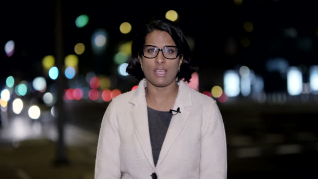 Indian female news reporter reporting live from the city center at night