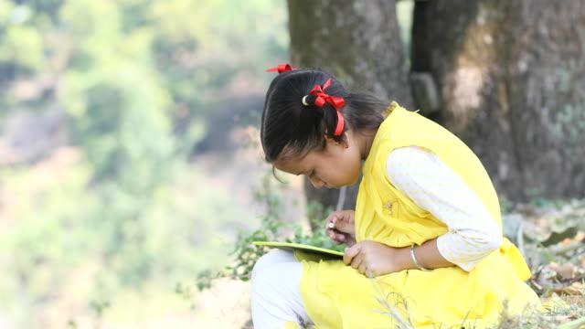 Indian girl writing on slate