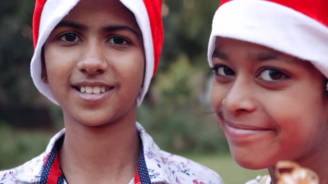 indian kids wearing santa hats and holding gifts looking at camera with big black eyes and smiling - weihnachtsmütze stock-videos und b-roll-filmmaterial