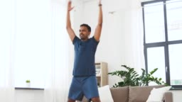 indian man doing jumping jack exercise at home