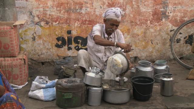 ZI Indian man preparing fresh coffee at outdoor market / Rajkot, Gujarat, India