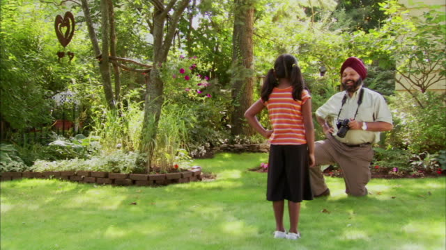 ws indian man taking picture of granddaughter (6-7) in garden, halifax, nova scotia, canada - see other clips from this shoot 1464 stock videos and b-roll footage