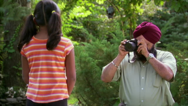 ms indian man taking picture of granddaughter (6-7) in garden, halifax, nova scotia, canada - see other clips from this shoot 1464 stock videos and b-roll footage