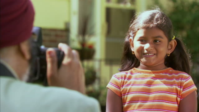 cu selective focus indian man taking picture of granddaughter (6-7) in garden, halifax, nova scotia, canada - see other clips from this shoot 1464 stock videos and b-roll footage