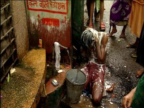 Indian man washes himself in street Calcutta