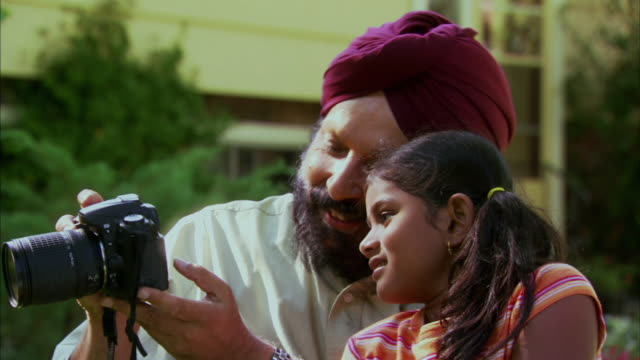 cu indian man with granddaughter (6-7) looking at picture in digital camera in garden, halifax, nova scotia, canada - see other clips from this shoot 1464 stock videos and b-roll footage