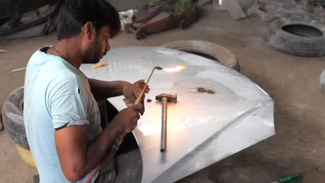 Indian mechanic manual worker repairing car bonnet
