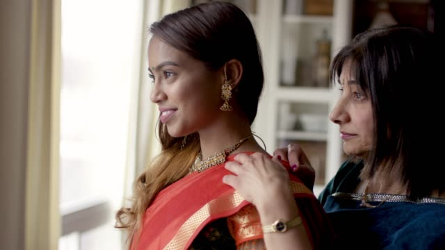 indian mother helping her adult daughter get dressed - sari stock videos & royalty-free footage
