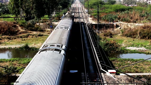Indian passenger train crossing water canal bridge