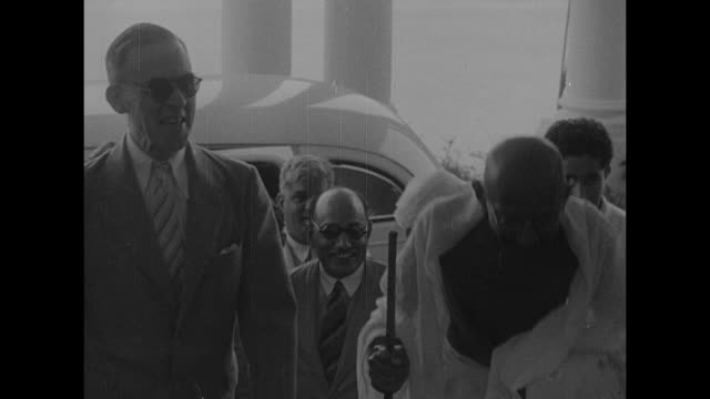 stockvideo's en b-roll-footage met indian political activist mohandas gandhi getting out of car and greeted by british envoy stafford cripps in front of cripps's residence; they walk... - mahatma gandhi