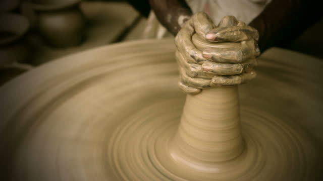 indian potter's skilled hand shaping pot on manual pottery wheel - potter stock videos & royalty-free footage