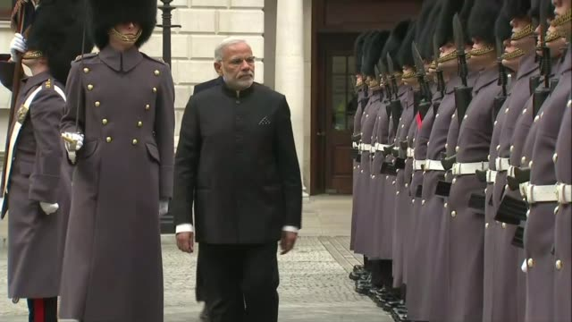 Indian Prime Minister Narendra Modi visit Whitehall Modi inspecting Guard of Honour with Prime Minister David Cameron MP along behind Military band...