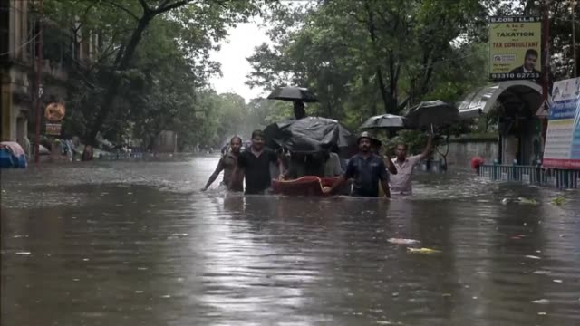 Indian rickshaw pullers carry students through water logged streets in Kolkata as torrential rains claim the lives of as many as 48 lives in eastern...
