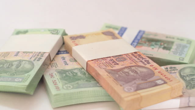 Indian Rupee, INR, being given away and taken back on a table