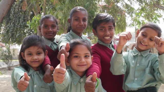 indian school students wearing uniform wishing the best of luck with their thumbs' up - 数人点の映像素材/bロール