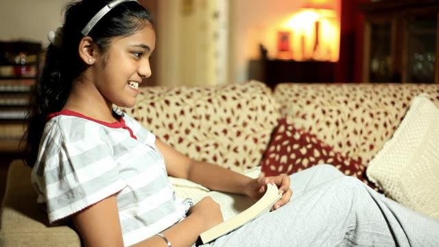 Indischen teenager-Mädchen rehearsing, während Sie ein Buch lesen
