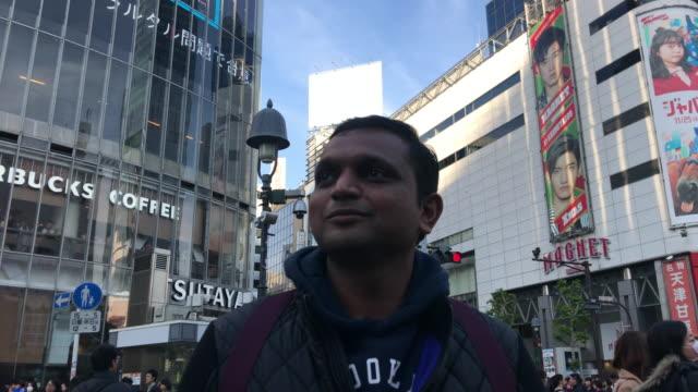 indian tourists crossing the scramble intersection in shibuya - tourist点の映像素材/bロール
